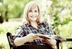 Porträt der reifen Frau sitzend auf Bank- und Lesebuch in g Lizenzfreies Stockbild