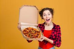 Porträt der reizend unterhaltenden jungen Frau, die Pizza hält Stockfoto