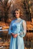 Porträt der romantischen Frau in einem Kleid auf der Bank des Flusses Lizenzfreie Stockbilder