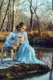 Porträt der romantischen Frau in einem Kleid auf der Bank des Flusses Lizenzfreie Stockfotos