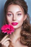 Porträt der romantischen jungen Frau mit der rosa Blume, die Kamera auf blauem Hintergrund betrachtet Frühlingsmodefoto Inspirati Stockbilder