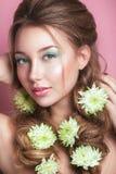 Porträt der romantischen jungen Frau mit grüner Blume und des Makes-up, das Kamera betrachtet Frühlingsmodefoto Stockfotografie
