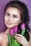 Porträt der romantischen jungen Frau mit Tulpen blühen und das Make-up, das Kamera betrachtet Frühlingsmodefoto Lizenzfreies Stockfoto