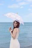 Porträt der Rothaarigefrau am Strand mit Regenschirm Stockfotografie