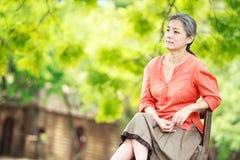 Porträt der ruhigen reifen Frau im Garten Lizenzfreies Stockbild