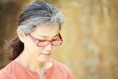 Porträt der ruhigen reifen Frau im Garten Stockbilder