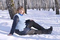 Porträt der russischen Frau, die auf Schnee im Birkenholz sitzt lizenzfreie stockfotos