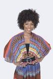 Porträt der schönen Afroamerikanerfrau in der traditionellen Abnutzung, die über grauem Hintergrund steht Stockfotos