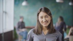 Porträt der schönen Asiatin im modernen Büro Junge erfolgreiche Geschäftsfrau, welche die Kamera, lächelnd betrachtet Stockbild
