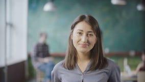 Porträt der schönen Asiatin im modernen Büro Junge erfolgreiche Geschäftsfrau, welche die Kamera, lächelnd betrachtet Lizenzfreie Stockbilder