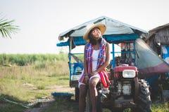 Porträt der schönen Asiatin sitzend auf Minitraktor am cou Lizenzfreie Stockfotografie
