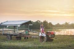 Porträt der schönen Asiatin sitzend auf Minitraktor am cou Lizenzfreie Stockbilder