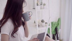 Porträt der schönen attraktiven Asiatin, die den Computer oder Laptop halten einen warmen Tasse Kaffee verwenden oder des Tees be stock video footage