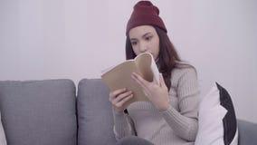 Porträt der schönen attraktiven Asiatin, die ein Buch beim Sitzen auf dem Sofa liest, wenn im Wohnzimmer sich zu Hause entspannen stock video footage