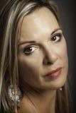 Porträt der schönen blonden älteren Frau mit silbernem Ohrring Stockfoto