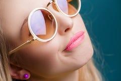 Porträt der schönen blonden Frau in der Sonnenbrille auf blauem Hintergrund Sorgloser Sommer Abschluss oben Lizenzfreies Stockbild