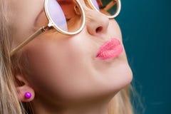 Porträt der schönen blonden Frau in der Sonnenbrille auf blauem Hintergrund Sorgloser Sommer Abschluss oben Stockfotografie