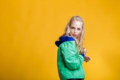 Porträt der schönen blonden Frau in der Sonnenbrille und in der blauen grünen Jacke auf gelbem Hintergrund Hippie-Sommer Stockfotos