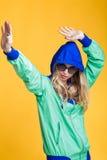 Porträt der schönen blonden Frau in der Sonnenbrille und in der mit Kapuze Jacke des blauen Grüns auf gelbem Hintergrund Hippie-S Stockfotografie