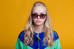 Porträt der schönen blonden Frau in der Sonnenbrille und in der mit Kapuze Jacke des blauen Grüns auf gelbem Hintergrund Hippie-S Stockbild