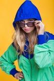 Porträt der schönen blonden Frau in der Sonnenbrille und in der mit Kapuze Jacke des blauen Grüns auf gelbem Hintergrund Hippie-S Stockbilder