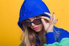 Porträt der schönen blonden Frau in der Sonnenbrille und in der mit Kapuze Jacke des blauen Grüns auf gelbem Hintergrund Hippie-S Lizenzfreie Stockfotografie