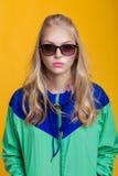 Porträt der schönen blonden Frau in der Sonnenbrille und in der mit Kapuze Jacke des blauen Grüns auf gelbem Hintergrund Hippie-S Lizenzfreie Stockbilder