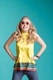 Porträt der schönen blonden Frau in der Sonnenbrille und in gelbem Hemd, die auf blauen Hintergrund springen Sorgloser Sommer Stockfotografie