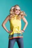 Porträt der schönen blonden Frau in der Sonnenbrille und in gelbem Hemd, die auf blauen Hintergrund springen Sorgloser Sommer Lizenzfreie Stockbilder