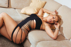 Porträt der schönen blonden Frau, die auf Couch sich entspannt Lizenzfreie Stockfotografie
