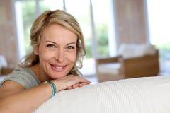 Porträt der schönen blonden Frau, die auf Sofa sich lehnt Stockfotos
