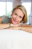 Porträt der schönen blonden Frau, die auf Sofa sich lehnt Stockfotografie