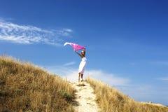 Porträt der schönen blonden Frau im weißen Kleid, das auf Wind mit Schal nahe Meer steht Stockfotografie