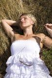 Porträt der schönen blonden Frau im weißen Kleid, das auf Wind mit Schal nahe Meer unter gelbem Gras steht Stockfoto