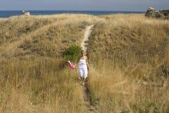 Porträt der schönen blonden Frau im weißen Kleid, das auf Wind mit Schal nahe Meer unter gelbem Gras steht Lizenzfreies Stockfoto
