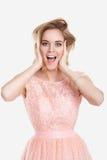 Porträt der schönen blonden sinnlichen Frau im rosa Cocktailkleid auf grauem Hintergrund Stockfotografie