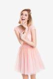 Porträt der schönen blonden sinnlichen Frau im rosa Cocktailkleid auf grauem Hintergrund Stockbild