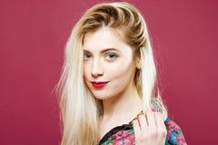 Porträt der schönen Blondine im bunten Hemd, welches die Kamera auf rosa Hintergrund betrachtet Hübsches Mädchen wirft im Studio  lizenzfreies stockbild
