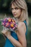 Porträt der schönen Blondine mit Blumenstrauß von Blumen Stockbild