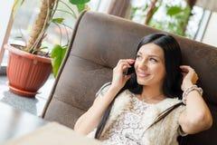Porträt der schönen Brunettefrau, die den Spaß sitzt in einem Restaurantaufenthaltsraum oder -Kaffeestube und spricht am Mobilhan lizenzfreie stockfotografie