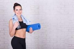 Porträt der schönen dünnen Frau mit der Yogamatte, die über whi steht Lizenzfreies Stockfoto