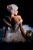 Porträt der schönen eleganten Braut, die mit Blumenstrauß sitzt Stockbilder