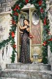 Porträt der schönen eleganten jungen Frau im herrlichen Abendkleid über Weihnachtshintergrund Lizenzfreie Stockfotografie