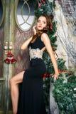 Porträt der schönen eleganten jungen Frau im herrlichen Abendkleid über Weihnachtshintergrund Stockfotos