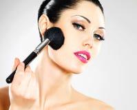 Schöne Frau, die Blusher auf Gesicht anwendet lizenzfreies stockbild
