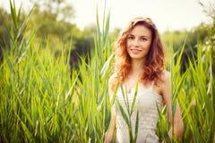 Porträt der schönen Frau im grünen Gras stockfotografie