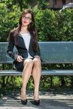 Porträt der schönen Geschäftsfrau sitzend auf der Bank Stockfoto
