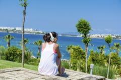 Porträt der schönen hörenden Musik der jungen Frau auf einem Seehintergrund stockfotografie