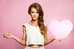 Porträt der schönen herrlichen Frau mit hellem Make-up des Zaubers und rosa Herzen in der Hand Lizenzfreies Stockbild