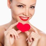 Porträt der schönen herrlichen Frau mit hellem Make-up des Zaubers und rotem Herzen in der Hand Stockfoto